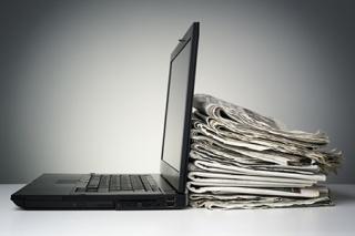 le mix contenu éditorial : un pc portable ouvert contre une pile de journaux